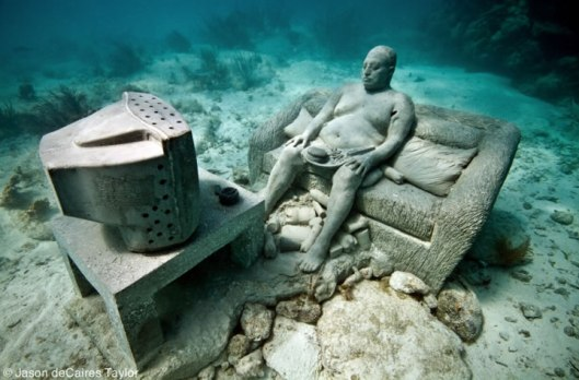 underwater museum mexico inertia man watching tv obese fast food junk fat lazy couch potato statue sculpture art